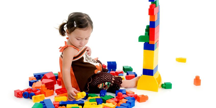 Young child playing with colorful plastic blocks.