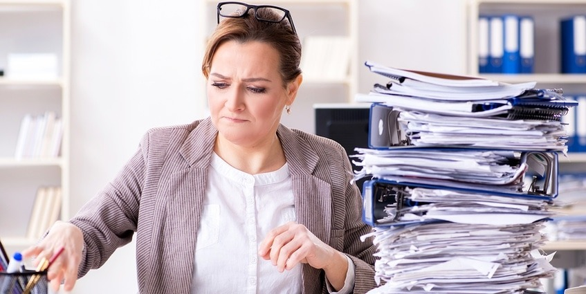 Woman at work with a stack of papers.