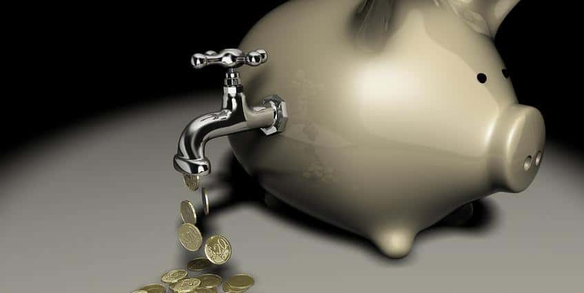 Piggy bank with a spigot pouring out coins.