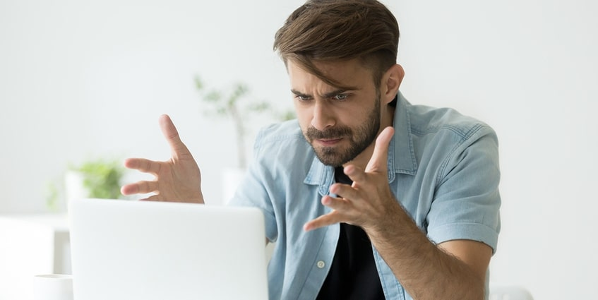 Man sitting in front of a computer appearing frustrated.