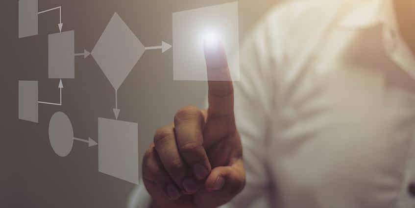 Man pointing to a graphic showing workflow with shapes.