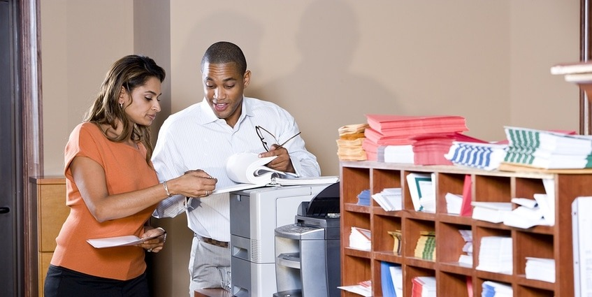 Two people in an office looking over documents.