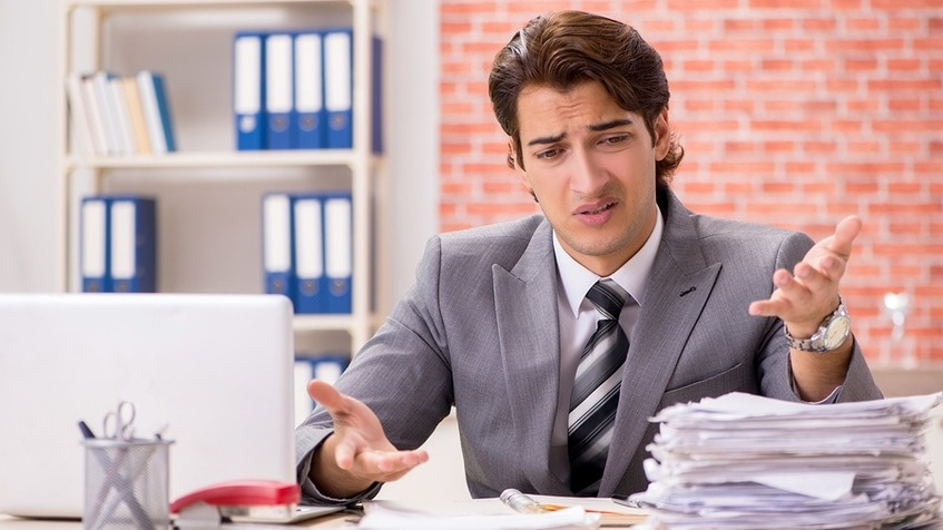 Man in a business suit looking frustrated at a pile of papers on his desk.